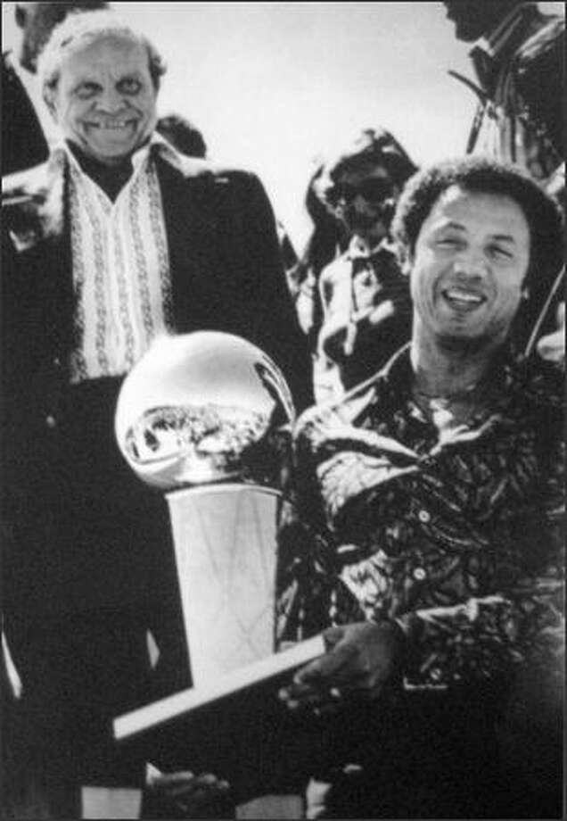 Seattle SuperSonics Coach Lenny Wilkens carries the NBA championship trophy as Sonics owner Sam Schulman follows him down the stairs from the Sonics chartered plane as it arrived in Seattle the afternoon of June 1979. (seattlepi.com file)