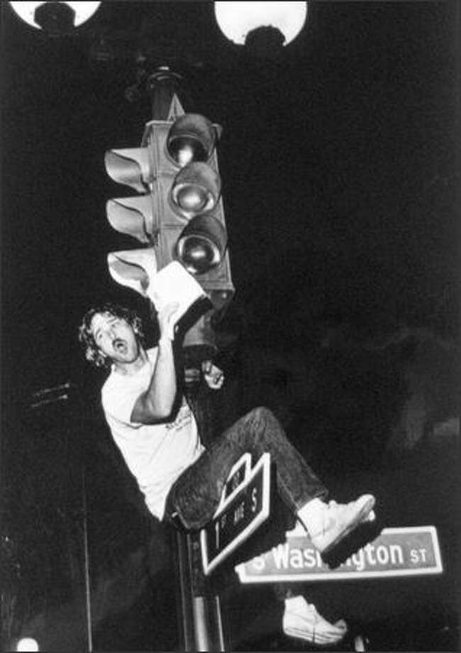A fan climbs a street light near Pioneer Square to celebrate the Sonics' victory. 1979. (seattlepi.com file)