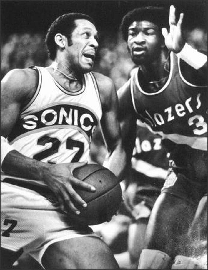"""Out of my way!"" appeared to be John Johnson's message as he drove past Portland's Calvin Natt (right) en route to the hoop in Kingdome action during the playoffs in 1980.  Johnson scored 21 points to help lead the Sonics past the Blazers, 120-110. (seattlepi.com file)"