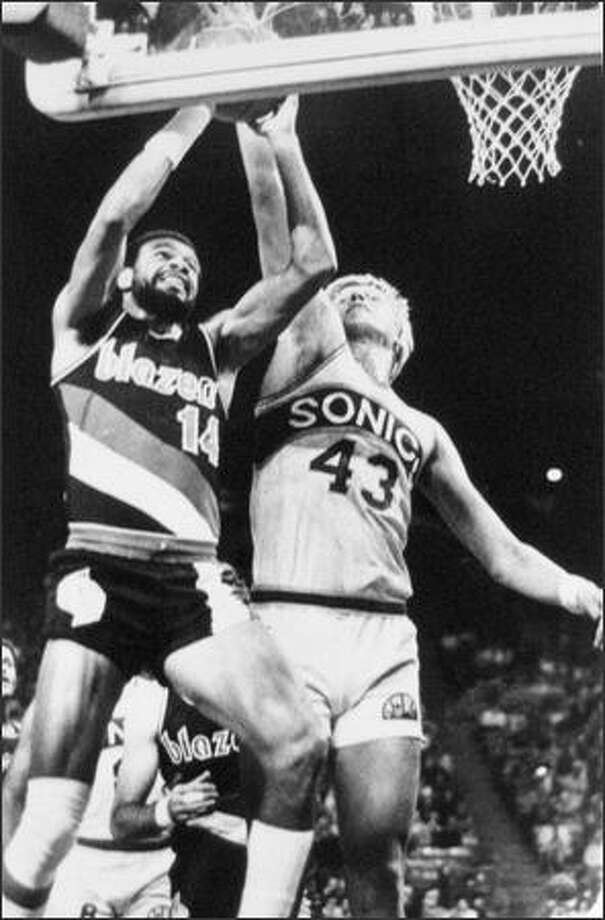Sonics' Jack Sikma (43) blocks as Blazers' Lionel Hollins (14) goes for a layup. 1978-79. (seattlepi.com file)