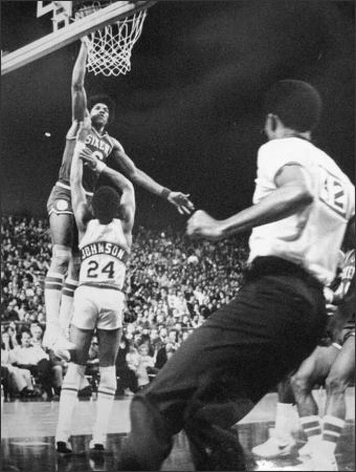 The Doctor, Julius Erving, operated on Dennis Johnson during this bit of action in December of 1978 in the Kingdome, going high over the Seattle guard for a patented dunk shot as the Philadelphia 76ers handed the Sonics their fifth straight loss, 103-95. (seattlepi.com file)