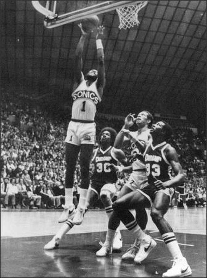 Seattle Sonic Gus Williams 91) goes for two points in first quarter action at the Seattle Center Coliseum during the third game between the Sonics and the Denver Nuggets in the NBA Western Conference finals. Watching are, from left, Nugget Darnell Hillman 930), Sonic John Johnson (22) and Nugget David Thompson (33). The Sonics won 105-91. (seattlepi.com file)