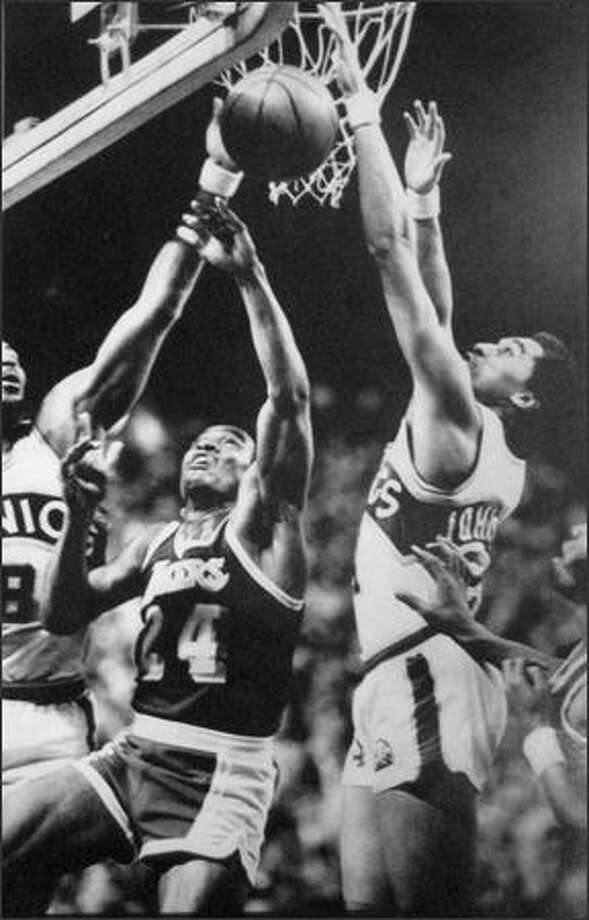 Los Angeles' Ron Boone (24) puts up a shot between Seattle's Lonnie Shelton (8) and Dennis Johnson (24) in April of 1979 in their NBA playoff game in Seattle.