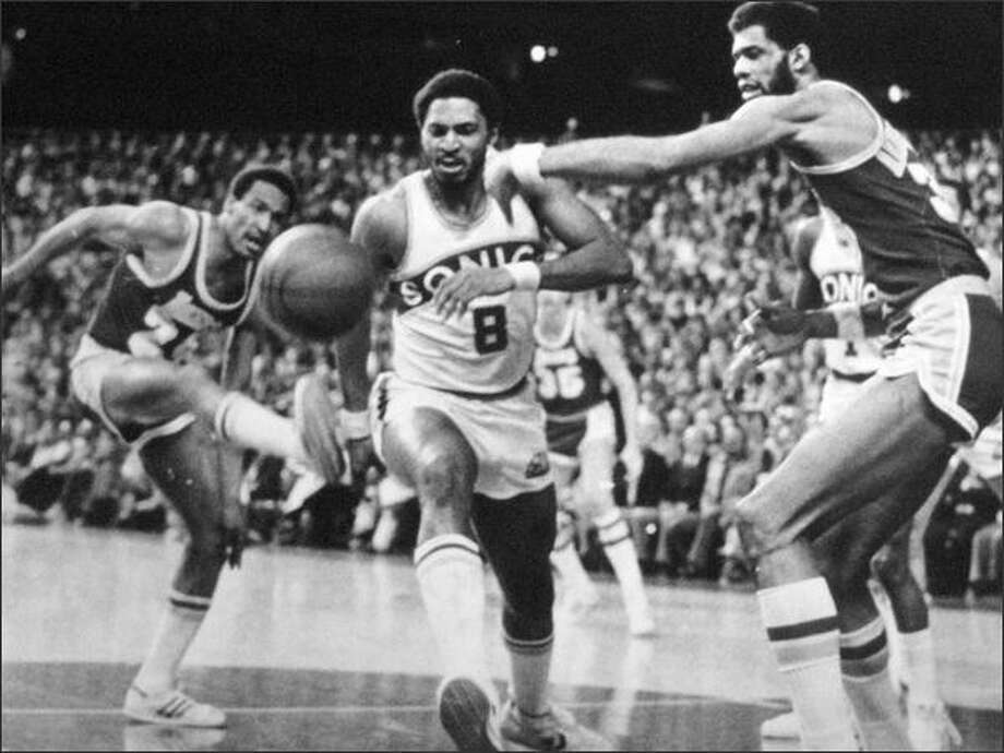 Lonnie Shelton (8) of the Sonics races Los Angeles' Kareem Abdul Jabbar, at right, for a loose ball during the second game of the NBA playoff series in 1979. Laker Ron Boone does a high kick at left. Dennis Johnson's jumper at the buzzer sent the game into overtime and the Sonics came on to win it, 108-103. (seattlepi.com file)