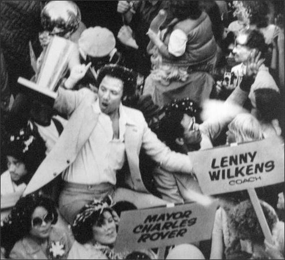 Seattle SuperSonics Coach Lenny Wilkens holds up the NBA World Championship trophy before some of the thousands of fans that lined Seattle streets June 4, 1979 in celebration of the Sonics victory over the Washington Bullets. Seattle welcomed their heroes with a noon-time parade. (seattlepi.com file)