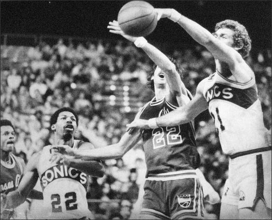 Dennis Awtrey (right) of the Sonics tried to pass as Gus Gerard of Kansas City (22) batted at the ball in Kingdome action March of 1979. Jackie Robinson (left) of Seattle followed the action. (seattlepi.com file)
