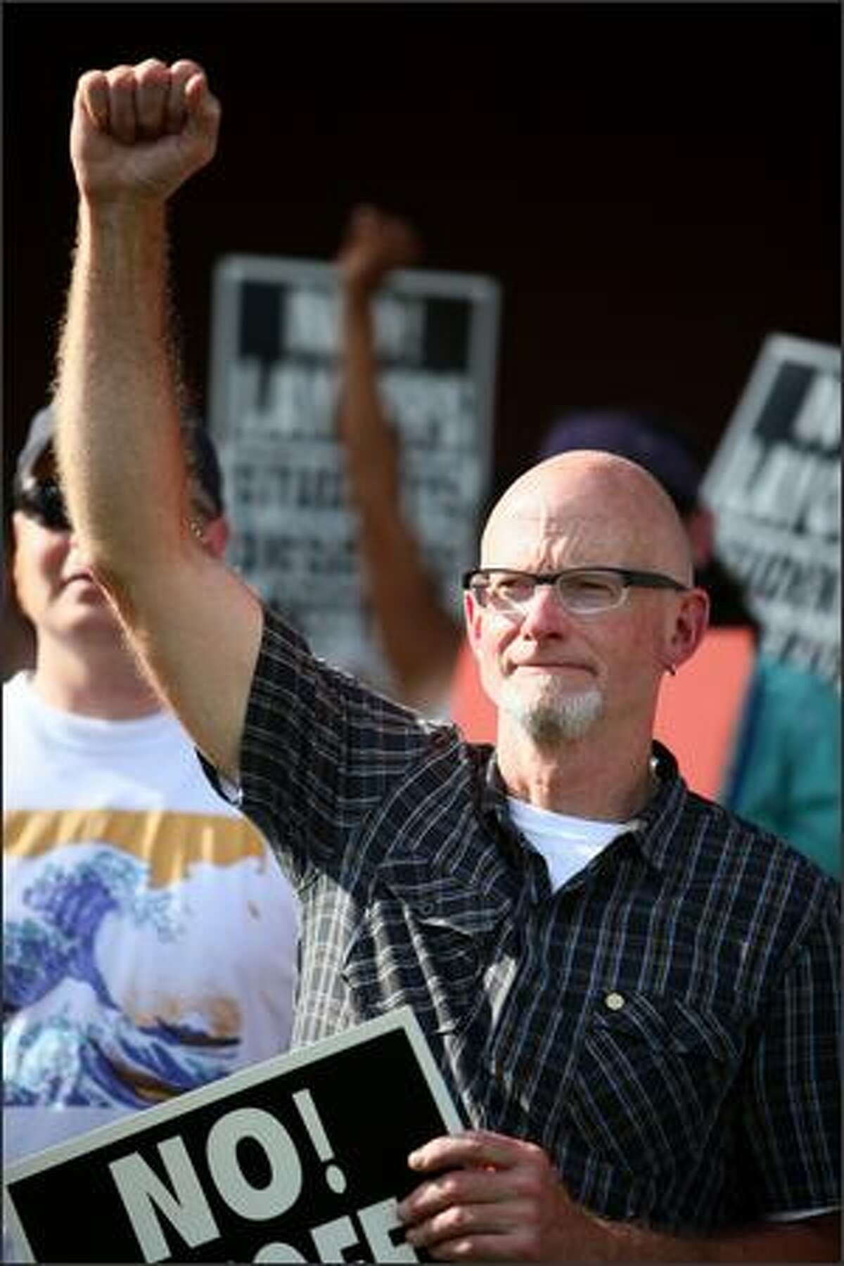 Laid off teacher Jim Jarosz, who worked at Hamilton Middle School, raises his fist with other laid off teachers during a protest in recent reduction in force (RIF) layoffs within Seattle Public Schools at the John Stanford Center for Educational Excellence on June, 3, 2009 in Seattle.