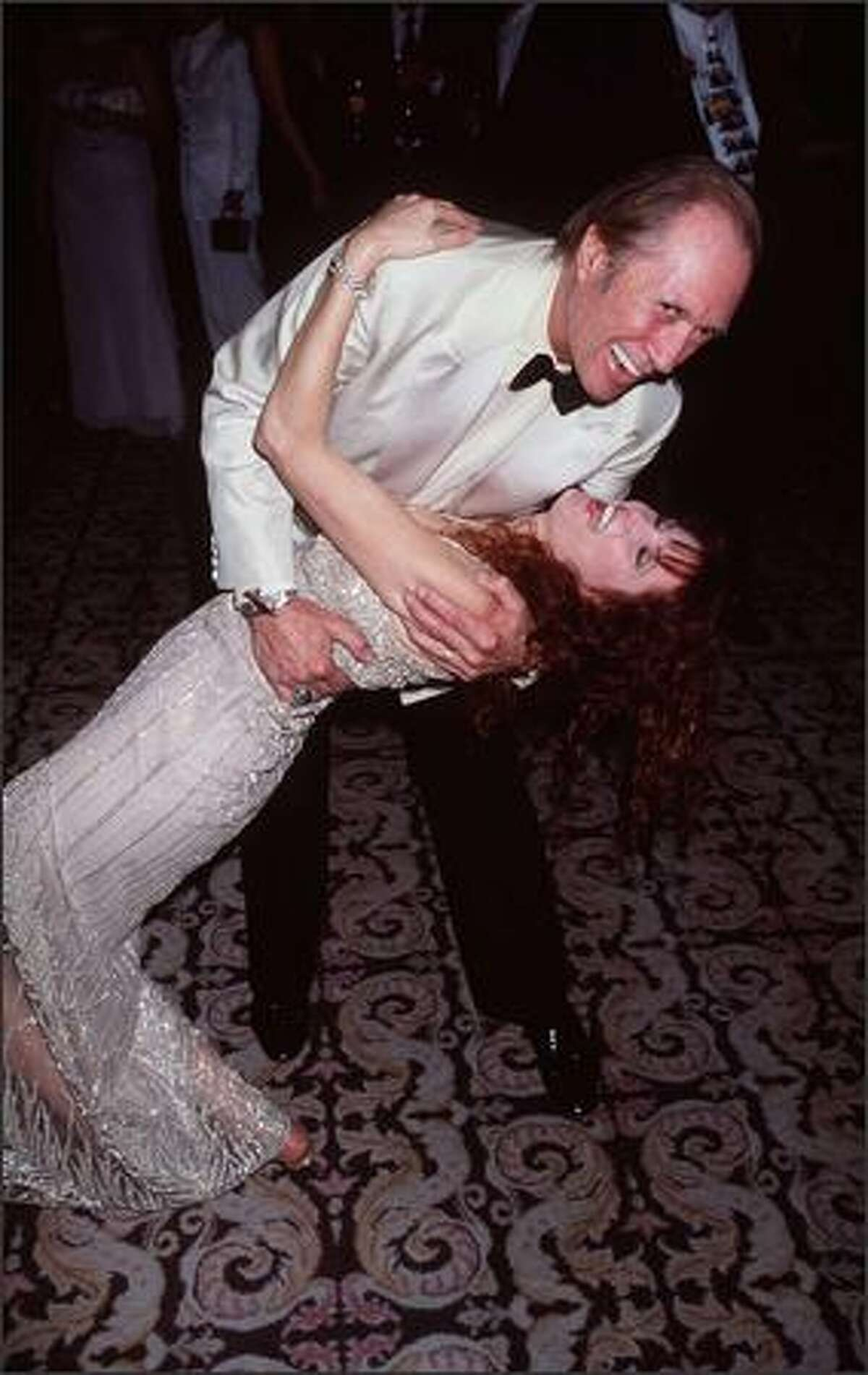 """Actor David Carradine dips his fourth wife, Marina, at the 50th Annual Directors Guild Awards March 6, 1998, in Century City, Calif. Carradine charged People Weekly of libel and claims the magazine violated a """"gentleman's agreement"""" to print a """"nice"""" article to settle another suit against Australia's Who Weekly, which identified Carradine's wife, Marina Benjamin, as a porn star. Los Angeles Superior court Judge Malcolm Mackey sided with People Weekly's story. (Photo by Brenda Chase/Online USA)"""