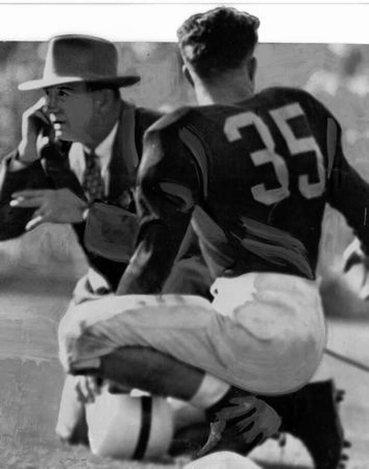 UW coach Pest Welch talks with a coaching aid in the press box while Quarterback Dick Ottele awaits instructions, 1946. Photo: P-I File
