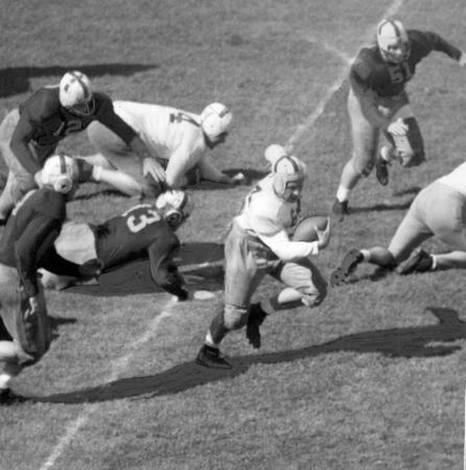 Husky Sam Robinson in the 1947 spring game. Also pictured are Doug Vickery (4), Frank Saksa (51), Leo Trask (13) and Bill Burnett (12). Photo: P-I File