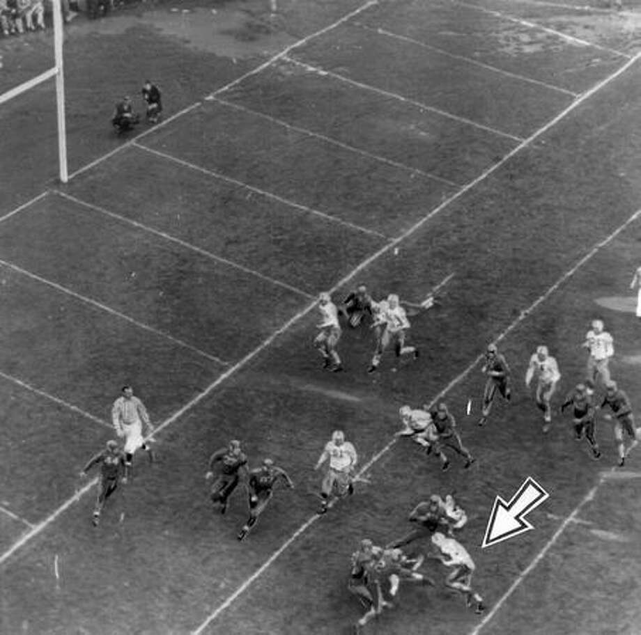 Maury Stacy (arrow), Washington halfback, is shown being brought down on the Oregon 8-yard line in the early minutes of a Nov. 1941 Oregon game at Portland. The Huskies moved to within inches of a touchdown on the series, but lost their scoring opportunity with a fumble. Photo: P-I File