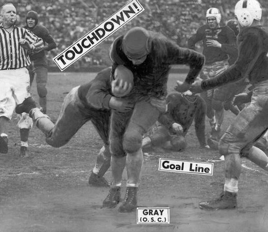 Dick Gray, Oregon State halfback, is shown booming across Washington goal line in the fourth quarter for the touchdown that sent the Huskies to a 7-to-6 defeat in Nov. 1945. Photo: P-I File