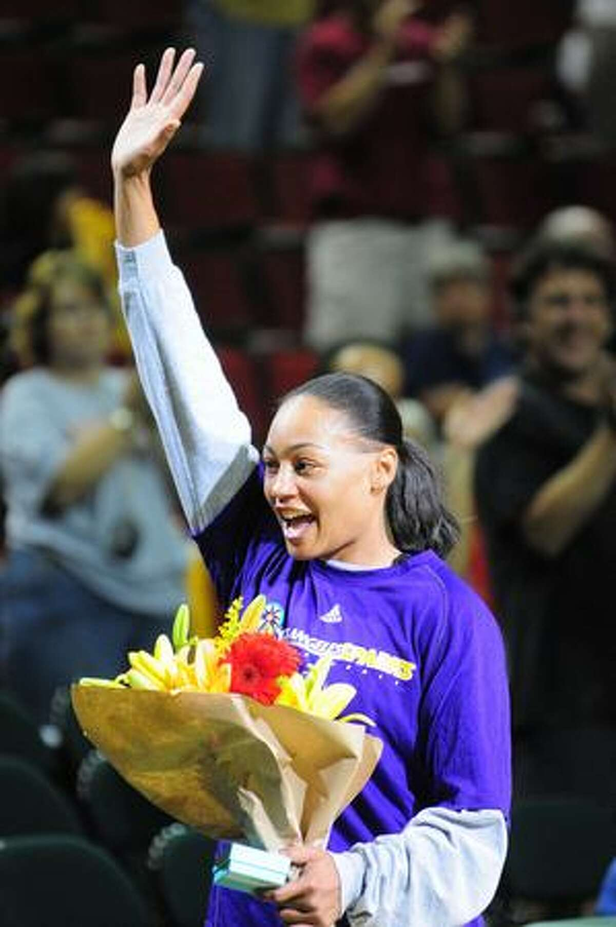 Betty Lennox of the Los Angeles Sparks waves to the crowd after being presented with flowers by Seattle Storm CEO Karen Bryant at the start of the game Wednesday July 23, 2009.