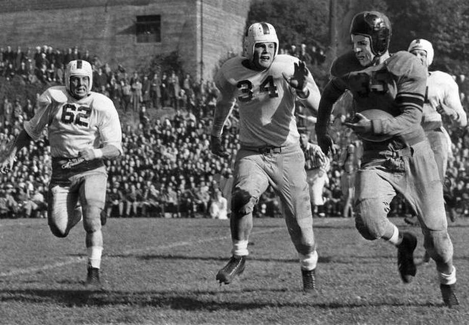 Vic Hartmann, Oregon State halfback, is shown being pursued by Husky Fullback Leo Task (62) and Center Bill McGovern (34) in a Nov. 1945 game in Portland. Washington won, 13 to 0. Photo: P-I File