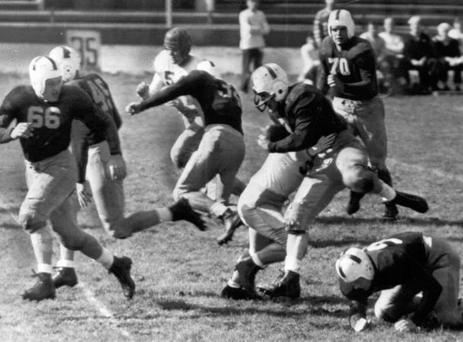 Fullback Keith DeCourcey of Washington is shown scoring one of his four touchdowns when the Huskies trounced Willamette 40 to 6. The Oct. 1944 game was in Portland. Photo: P-I File