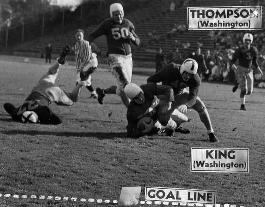 Leo Cantor, March Field fullback, is downed by Bob Zech (37) and Whitey King (49) deep in Husky territory. But the Flyers scored their first touchdown on a Cantor plunge four plays later. Nov. 1944. Photo: P-I File