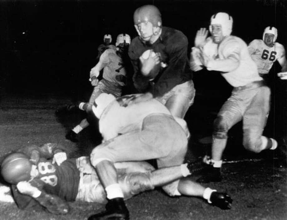 Gordon Gray, Southern California halfback, runs into the arms of a waiting Washington tackler, Oct. 1944, in Los Angeles. U.S.C. won 39-7 before 70,000 spectators. Photo: P-I File