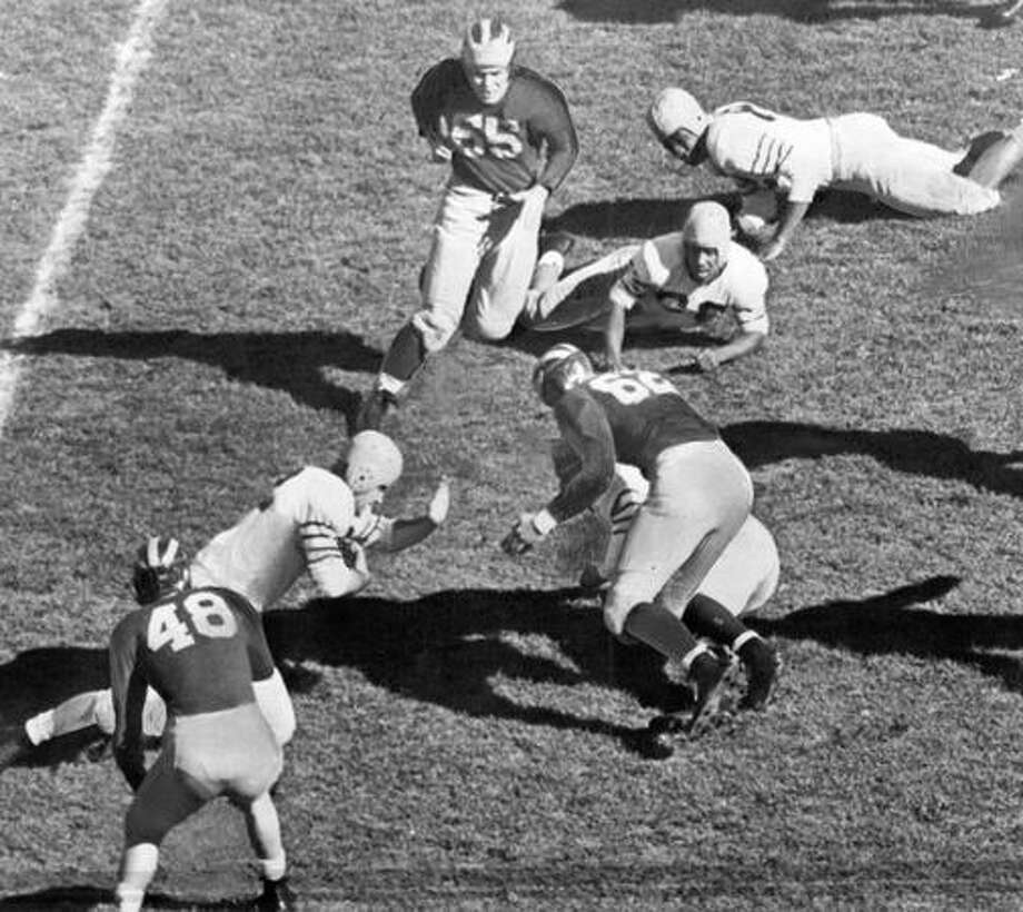 A Michigan player (Rykovich ) is stopped in an Oct. 1946. game against Washington. The Huskies won 13-9. Photo: P-I File