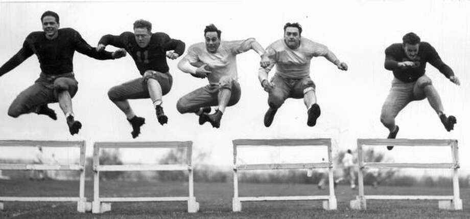 Fred Wehde, Neil Brooks, Fred Provo, Arnold Weinmeister, Dick Watson - all former servicemen - go over hurdles during a 1946 spring practice Photo: P-I File