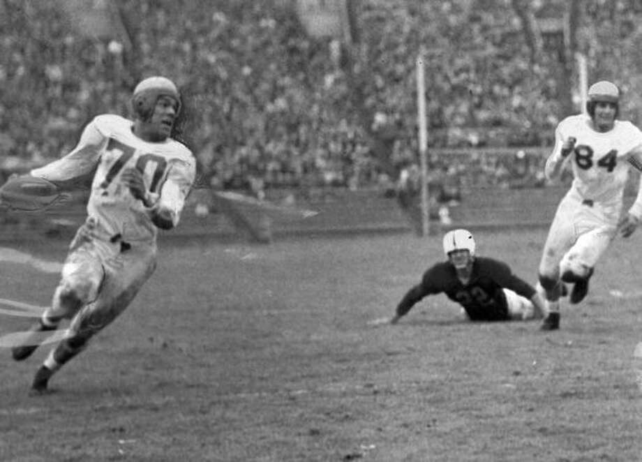 Bob Reynolds, Oregon halfback, in the first quarter of a Nov. 1946 game against Washington. In the back is Husky end Dick Brown. Photo: P-I File