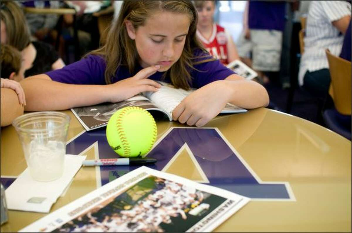 Livia T'sas, 11, reads a program in the Don James Center before a celebration of the UW softball team's College World Series championship title at Husky Stadium Sunday.