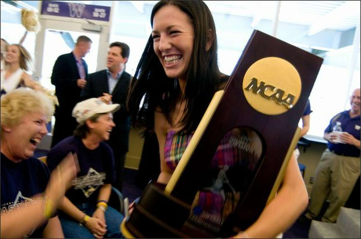 UW softball 2nd base Ashley Charters smiles while holding the trophy following a ceremony to celebrate their College World Series championship title, at Husky Stadium Sunday.