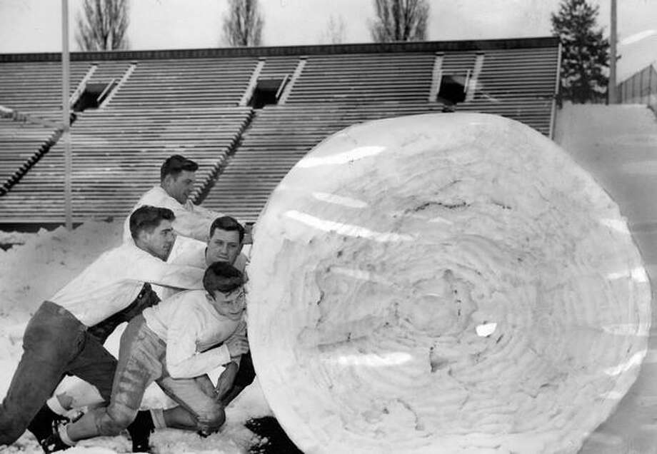 Seattle's heavy snowfall kept the University of Washington football team indoors in Nov. 1946. Putting their shoulders to a snowball are, left to right: Marshall Dallas, Bruce Rehn, Pete Foster and Harold Lloyd. Photo: P-I File