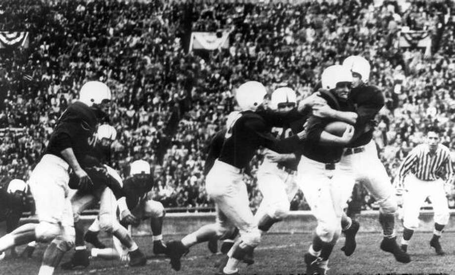 Husky players Gale Bruce and Herb Harlow stop Stanford's Bob Anderson in the second quarter of a Nov. 1947 game. Photo: P-I File