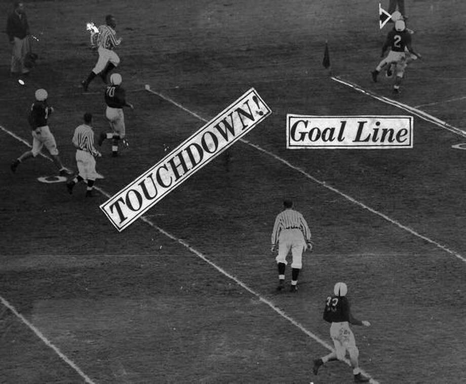 Brooks Biddle, Washington's right halfback, crosses the Stanford goal line for Washington's second touchdown in the second quarter of a Nov. 1947 game. Brooks raced around left end and went down the sidelines. Halfback Wayne Erickson (2) blocks Biddle from view. Photo: P-I File