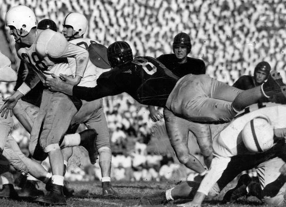 Husky halfback Gordy Hungar (38) fumbles in the second quarter of the 1947 game against California. Photo: P-I File