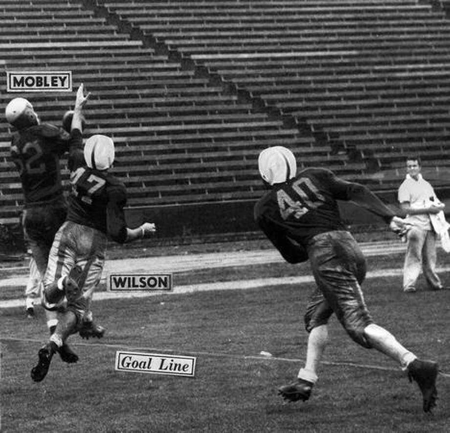 Oregon's Dick Mobley catches a pass from Earle Stelle. Husky defenders are J.R. Savage and Herb WIlson. The Oct. 1947 game ended in a 7-7 tie. Photo: P-I File