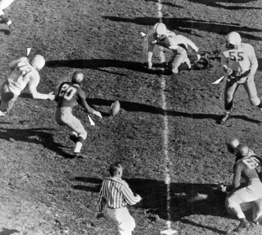 A fumble in the 1948 UW game against Notre Dame. Lancaster Smith is the Irish player (20). Washington players are John Prechek (78), Alf Hemstad (66) and Bill McGovern (55). Photo: P-I File