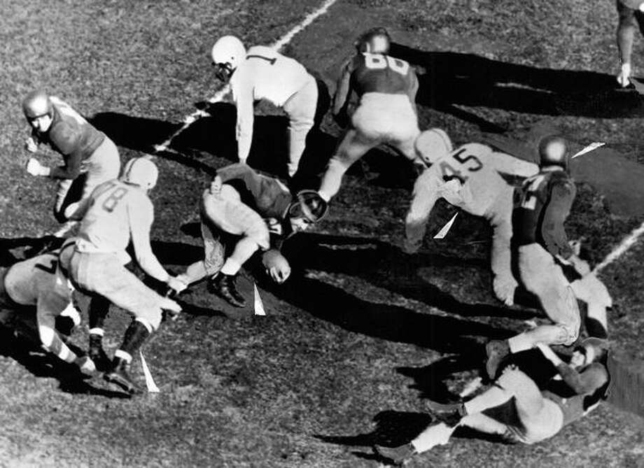 Husky John Prechek (78) tries to stop John Panelli of Notre Dame. The Irish won the Nov. 1948 game in South Bend, 46-0. Photo: P-I File