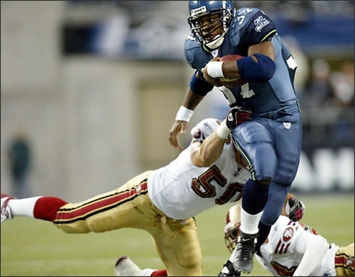 Seahawks running back Shaun Alexander rushes for a 10 yards and a first down as Solomon Bates of the 49ers pursues during the second quarter.