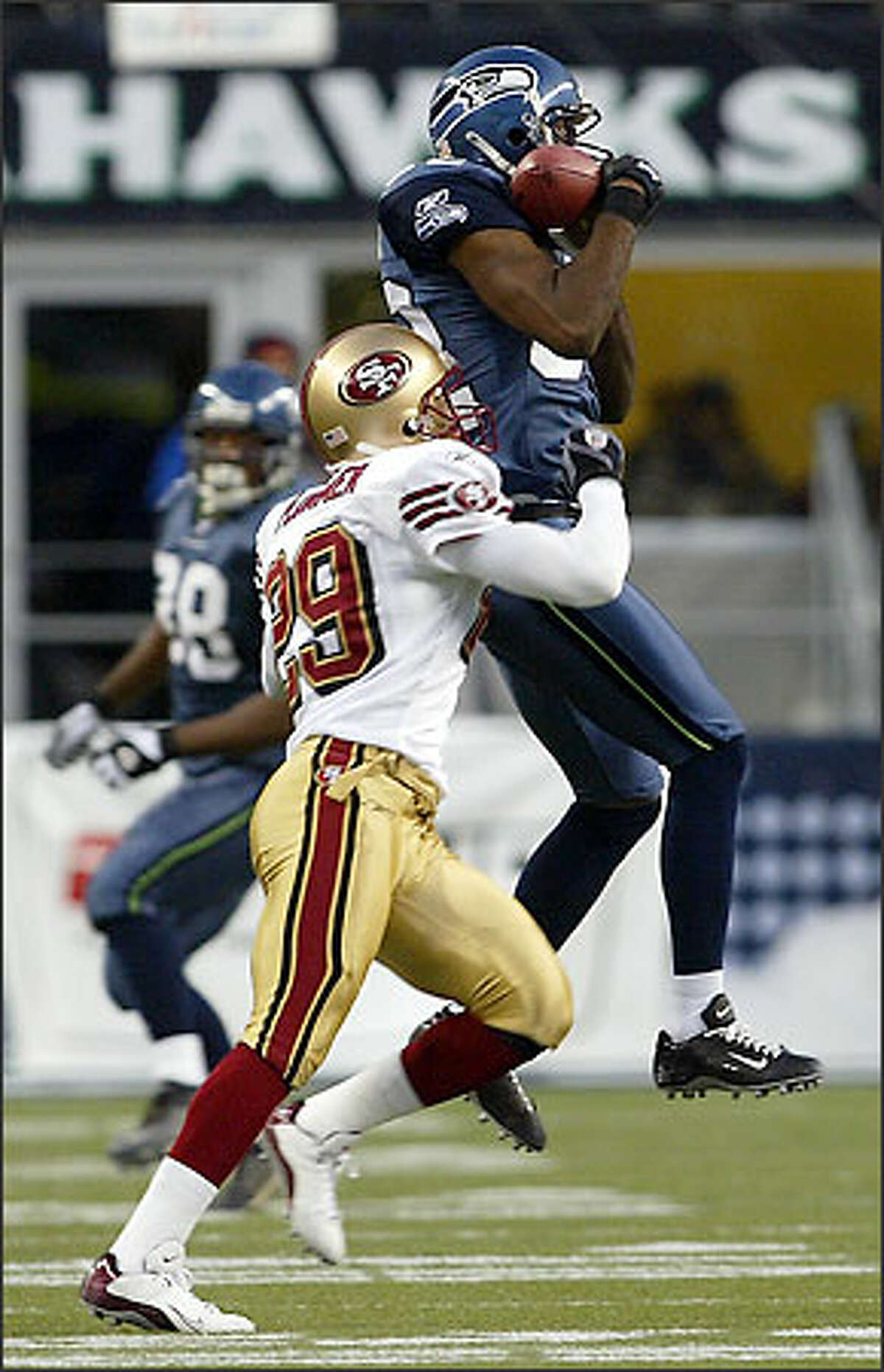 Seahawks' Alex Bannister makes a catch over 49er's Ahmed Plummer with 8:32 left in the second quarter of play at Seahawks Stadium.