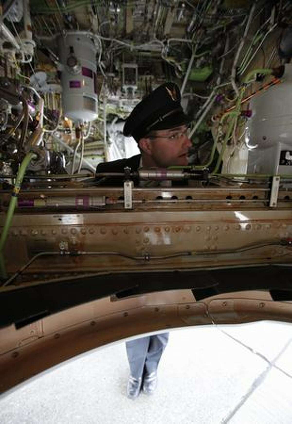 Alaska Airlines pilot Jeff Browand listens to questions from students while hanging out in the landing gear well.