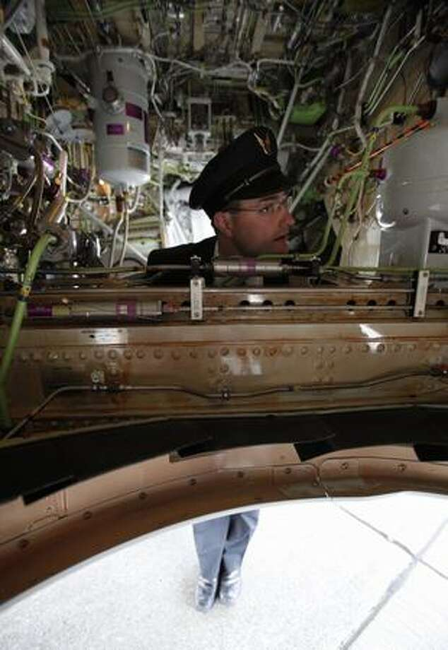 Alaska Airlines pilot Jeff Browand listens to questions from students while hanging out in the landing gear well. Photo: Clifford DesPeaux, Seattlepi.com