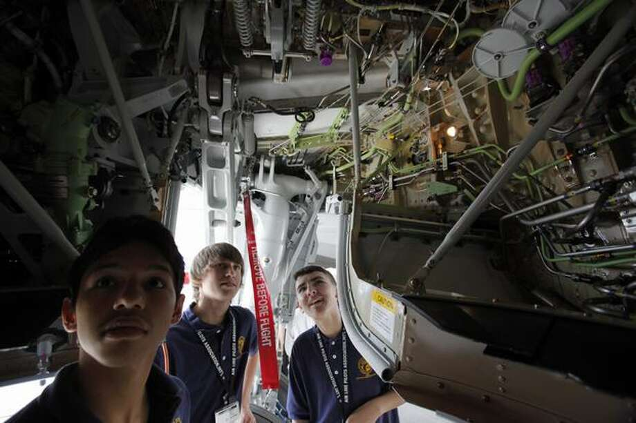 Aviation High School students, from left, Gerson Gutierrez, Treyce Hart and Phillip Romero look into the landing gear well before students take a ride on the first passenger flight of a new Boeing 737 being delivered to Alaska Airlines Monday. Photo: Clifford DesPeaux, Seattlepi.com