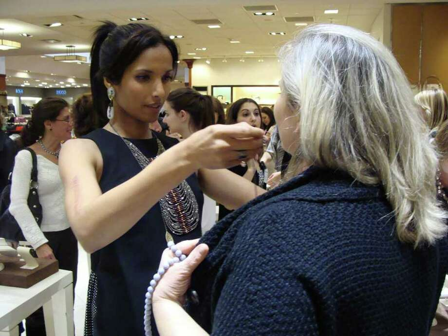 """Top Chef"" host and jewelry designer Padma Lakshmi places one of her necklaces on a customer at Mitchells of Westport on Thursday night. Photo: Meg Barone / Westport News freelance"