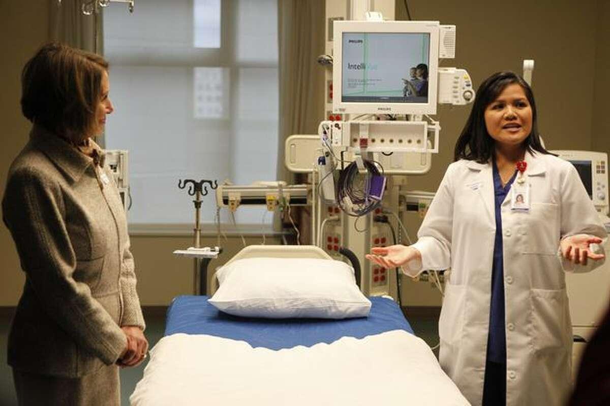 Caroline Truong explains some of Swedish Hospital's innovations as Speaker Nancy Pelosi listens.