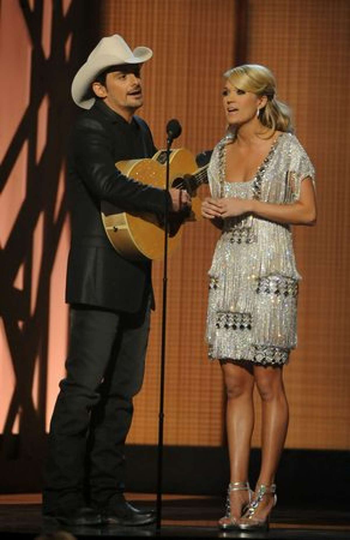 Hosts Brad Paisley and Carrie Underwood speak onstage.