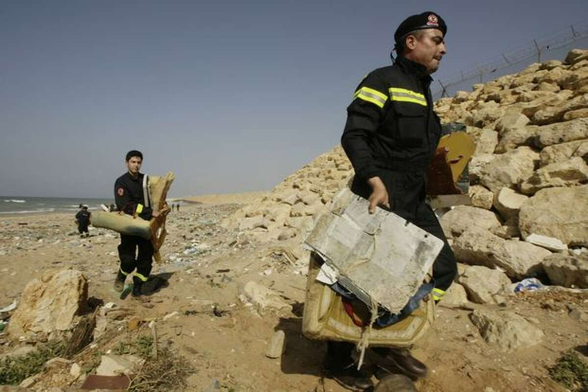 Lebanese civil defense workers carry parts and seats from the Ethiopian airliner that crashed off Lebanon's coast in the Beirut southern coastal suburb of Khaldeh on Jan. 29, 2010.