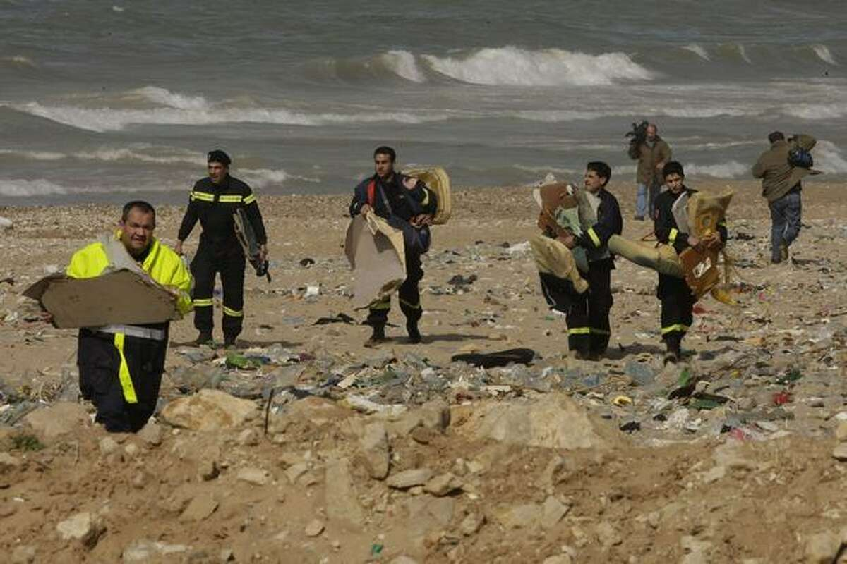 Lebanese civil defense workers carry parts from the Ethiopian airliner that crashed off Lebanon's coast in the Beirut southern coastal suburb of Khaldeh on Jan. 29, 2010.