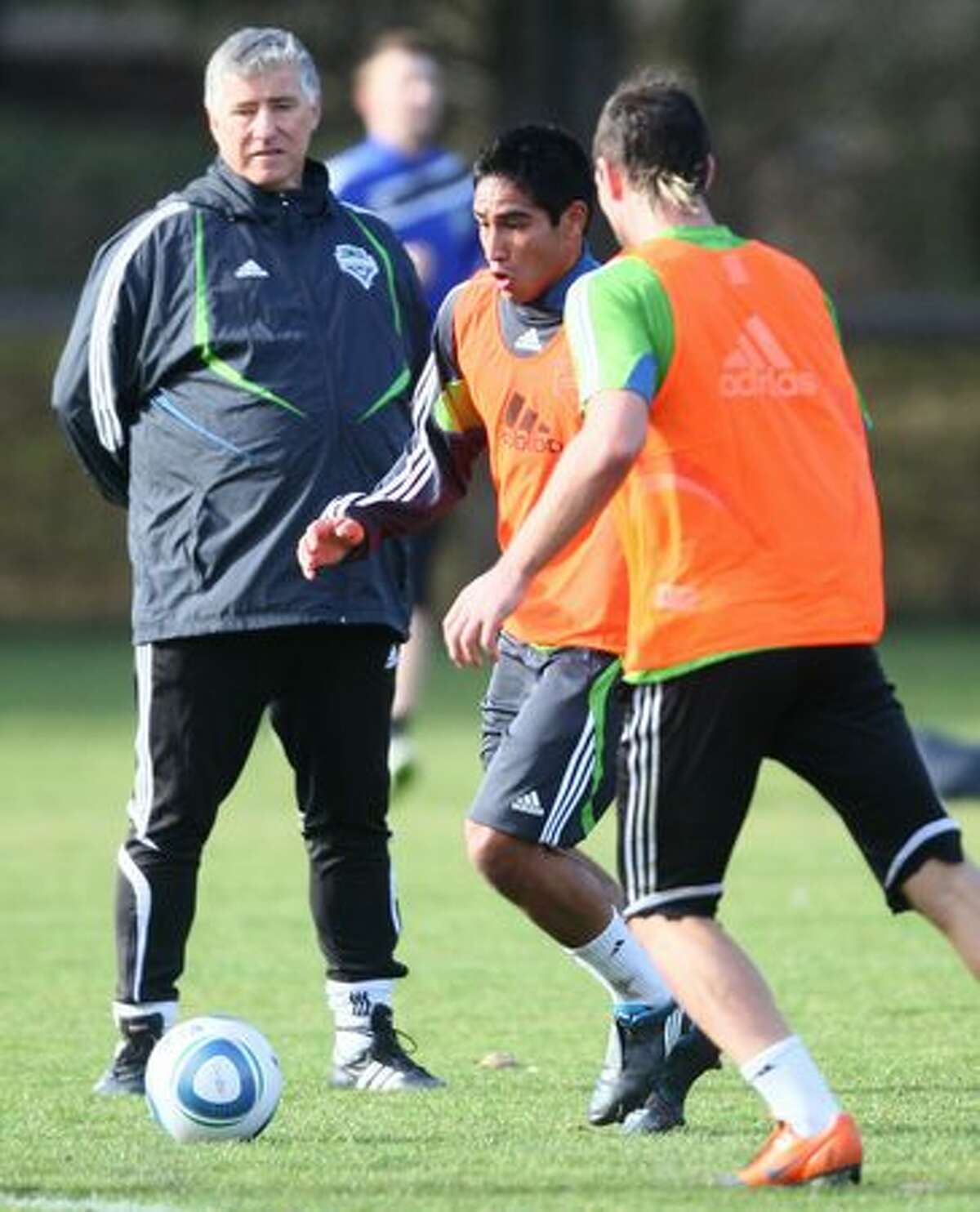 Seattle Sounders coach Sigi Schmid watches as draft pick David Estrada practices the first day of training camp on Monday at Starfire Sports Complex in Tukwila.