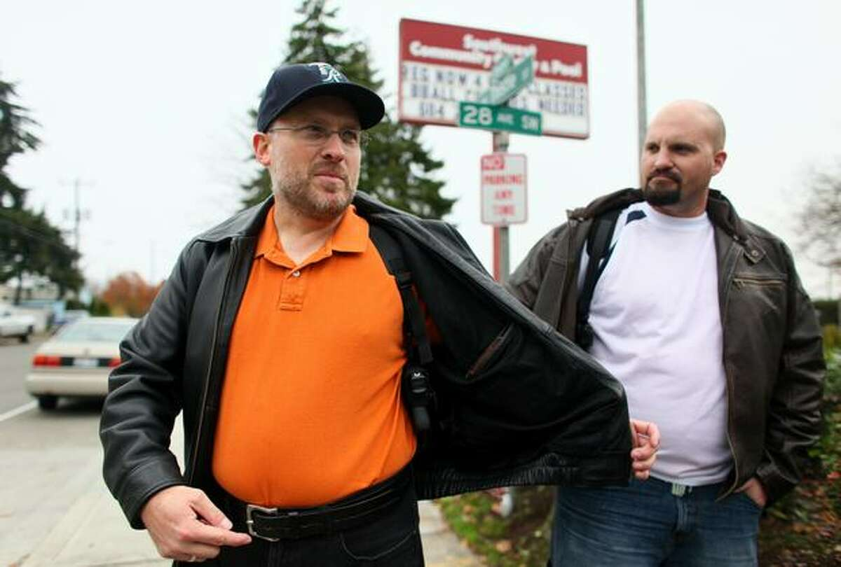 Bob Warden of Kent, left, and Jason Emm show their firearms to news crews in front of Southwest Community Center in West Seattle on Saturday, Nov. 14, 2009 after Warden entered the community center and was asked to leave. He carried his weapon into the building to begin a legal challenge to the City of Seattle's ban of firearms on city-owned property