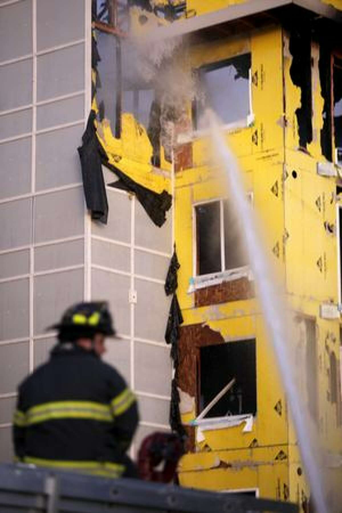 Firefighters spray water into a window during a four-alarm fire at a Renton Highlands apartment complex Tuesday evening.