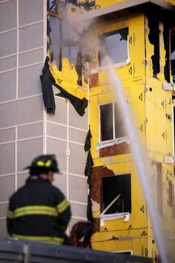 Firefighters spray water into a window during a four-alarm fire at a Renton Highlands apartment complex Tuesday evening. Photo: Clifford DesPeaux, Seattlepi.com