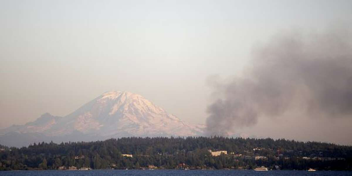 Smoke rises in front of Mount Rainier during a four-alarm fire at a Renton Highlands apartment complex Tuesday evening.