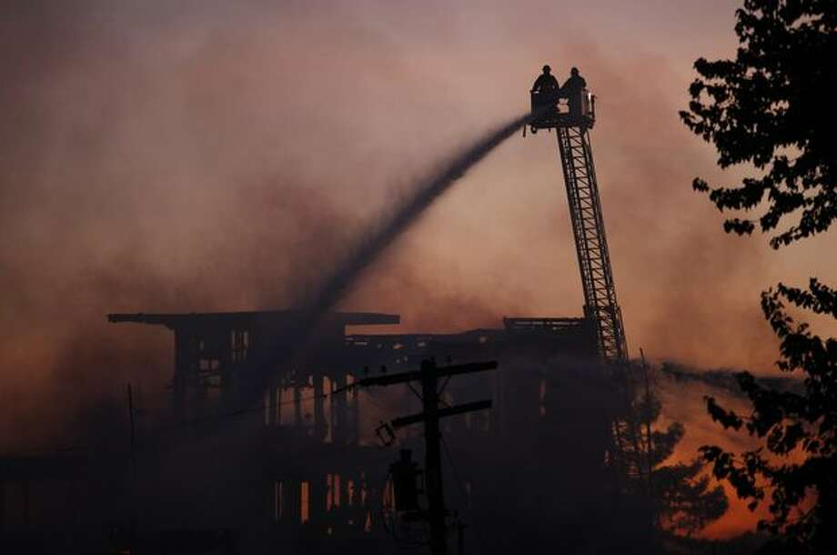 Firefighters spray water onto the complex during a four-alarm fire at a Renton Highlands apartment complex Tuesday evening. Photo: Clifford DesPeaux, Seattlepi.com