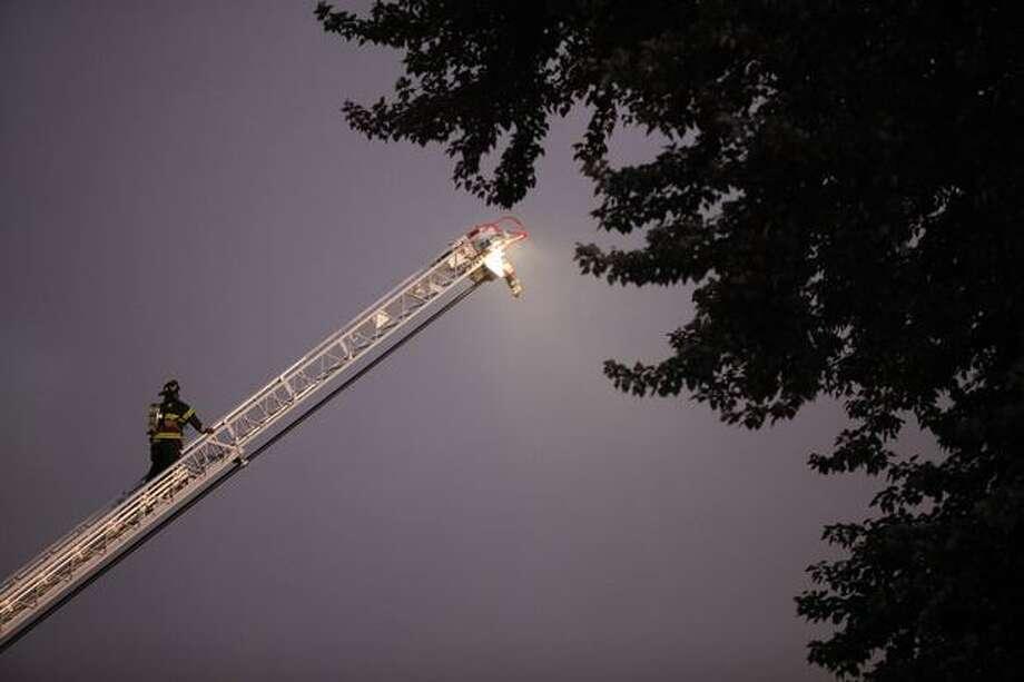 A firefighter climbs a ladder during a four-alarm fire at a Renton Highlands apartment complex Tuesday evening Photo: Clifford DesPeaux, Seattlepi.com